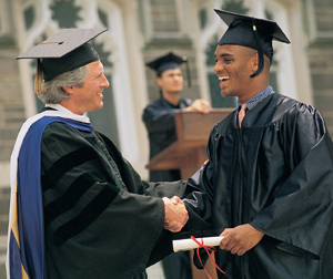 Man wearing cap and gown receiving diploma, graduating from college.