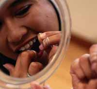 Reflection in mirror of a young girl flossing her teeth