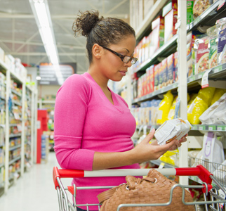 Woman at grocery store, looking at food label