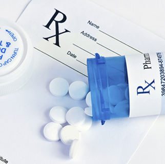 close up image of a prescription bottle spilled out on top of an RX pad of paper.